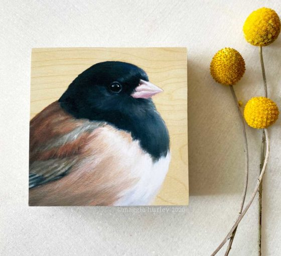 Overhead view of painting of a dark eyed junco on wood by Maggie Hurley